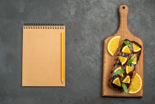 Above view of delicious cakes decorated with orange and chocolate on cutting board next to notebook