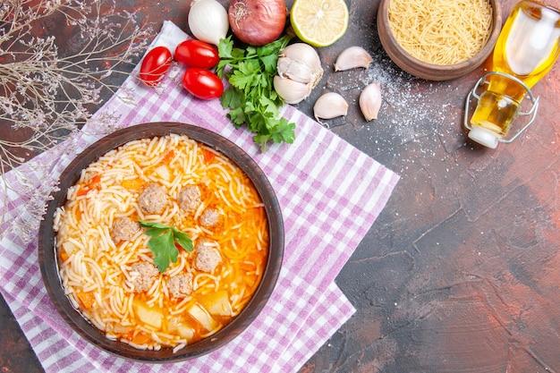 Sopra la vista di una deliziosa zuppa di pollo con noodles verdi e cucchiaio su una bottiglia di olio di asciugamano spogliata rosa aglio pomodori limone su sfondo scuro