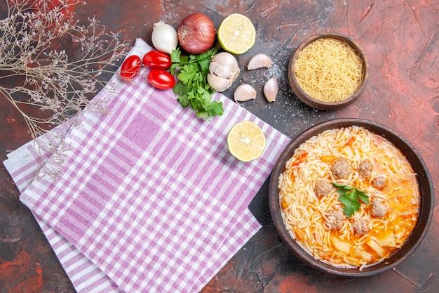 Sopra la vista di deliziosa zuppa di pollo con noodles verdi e cucchiaio su rosa asciugamano spogliato bottiglia di olio aglio pomodori limone e notebook su sfondo scuro