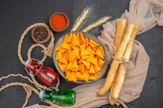 Sopra la vista di deliziose patatine fritte bottiglie di peperoni su asciugamano e corda su sfondo nero