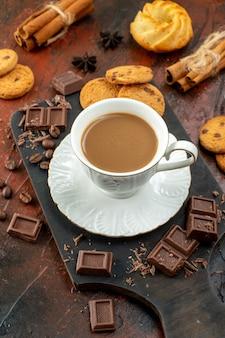 Sopra la vista di un delizioso caffè in una tazza bianca su un tagliere di legno, biscotti, cannella, lime, barrette di cioccolato su sfondo di colore misto