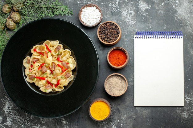 Sopra la vista di deliziose conchiglie con verdure e verdure su un piatto e un coltello e diverse spezie accanto al taccuino su sfondo grigio