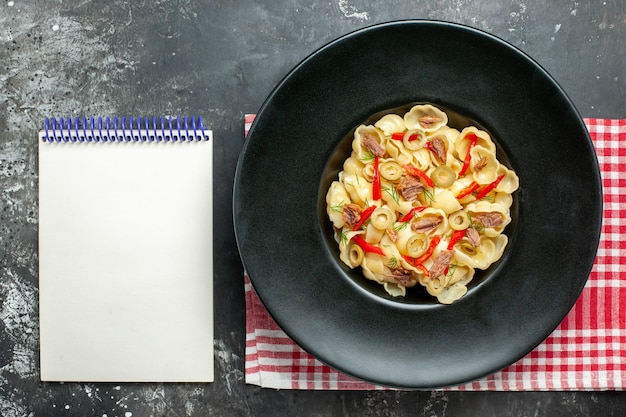 Above view of delicious conchiglie with vegetables and greens on a plate and knife on red stripped towel and notebook on gray background