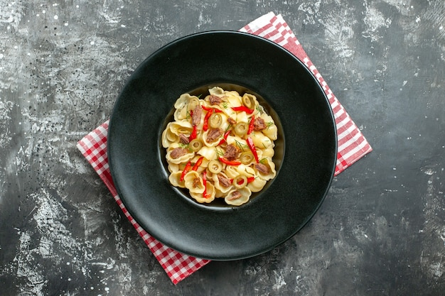 Above view of delicious conchiglie with vegetables on a plate and knife on red stripped towel on gray background