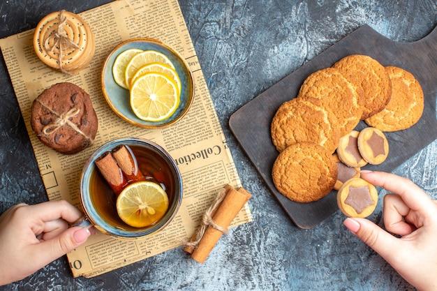 Sopra la vista di deliziosi biscotti e una tazza di tè nero con cannella e limone su un vecchio giornale