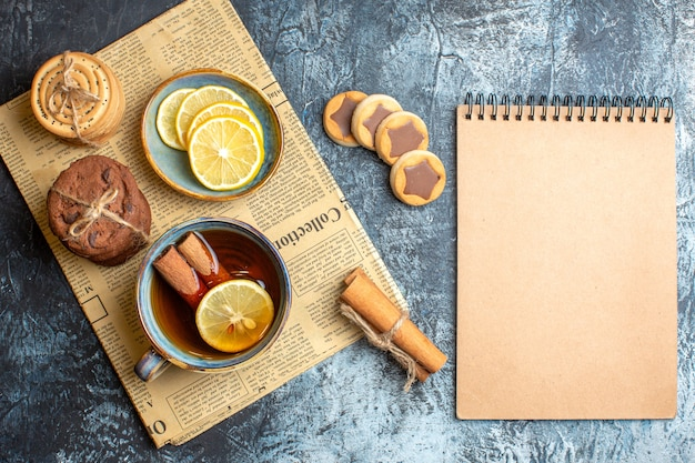 Above view of delicious cookies and a cup of black tea with cinnamon on an old newspaper next to spiral notebook on dark background