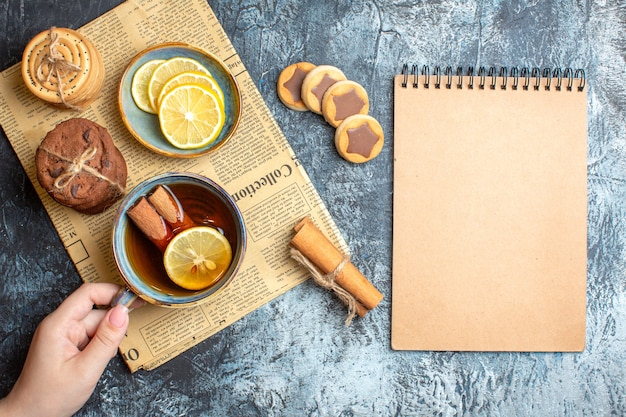 Above view of delicious cookies and hand holding a cup of black tea with cinnamon on an old newspaper