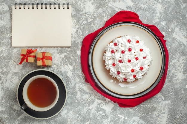 Above view of delicious creamy cake decorated with fruits on a red cloth