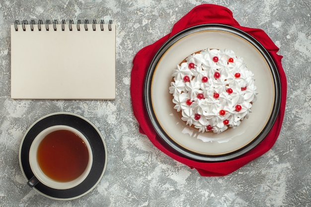 Above view of delicious creamy cake decorated with fruits on a red towel and a cup of black tea next to notebook on ice background