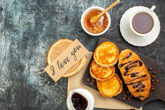Sopra la vista di deliziose frittelle di croissant su tagliere di legno una tazza di miele di tè nero su superficie scura