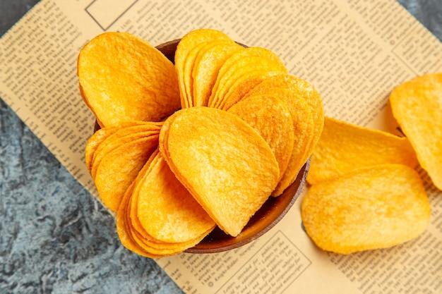 Sopra la vista di deliziose patatine fatte in casa sul giornale sul tavolo grigio