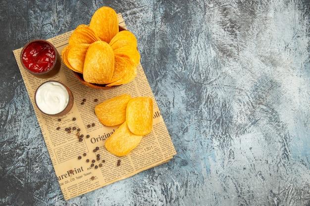 Sopra la vista di deliziose patatine fatte in casa e ketchup maionese ciotola di pepe sul giornale sul tavolo grigio