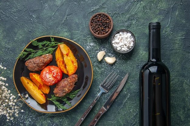 Above view of delicious meat cutlets baked with potatoes and tomatoes on a black plate spices garlics wine bottle on green black mix colors background