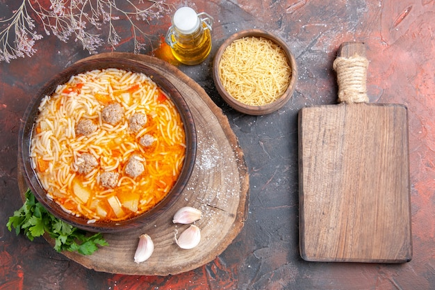 Above view of delicious noodle soup with chicken on tray greens oil bottle garlic on cutting board on dark background