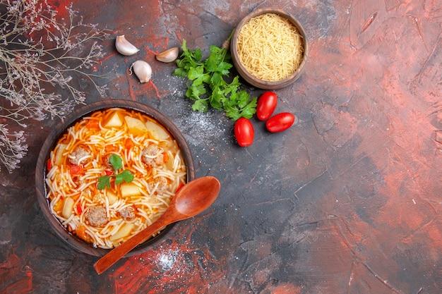 Sopra la vista della deliziosa zuppa di noodle con pollo e pasta cruda in una piccola ciotola marrone e cucchiaio di pomodori e verdure all'aglio sullo sfondo scuro