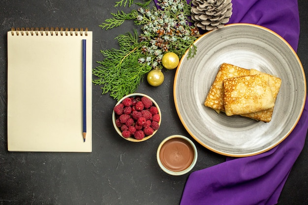 Above view of delicious pancakes on a white plate chocolate and raspberry decoration accessories on purple towel notebook with pen on black background
