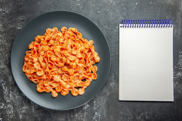 Above view of delicious pasta meal on a black plate for dinner and notebook on dark background