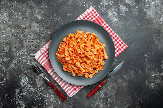 Above view of delicious pasta meal on a black plate for dinner on a red stripped cloth