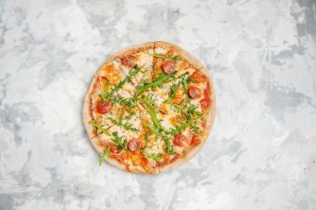 Sopra la vista di una deliziosa pizza con pomodori verdi su una superficie bianca macchiata con spazio libero