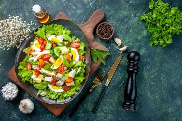 Vista sopra di una deliziosa insalata con ingredienti freschi sul tagliere di legno spezie bottiglia di olio garlics posate impostato su nero mix colori tabella Foto Gratuite