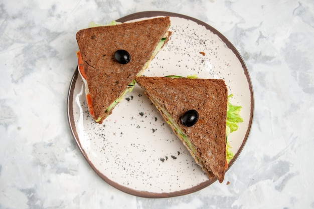 Above view of delicious sandwich with black bread decorated with olive on a plate on stained white surface