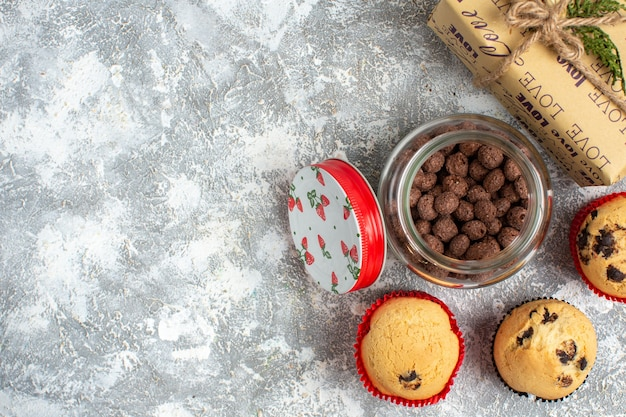 Above view of delicious small cupcakes and chocolate in a glass pot next to christmas gift on the left side on ice surface
