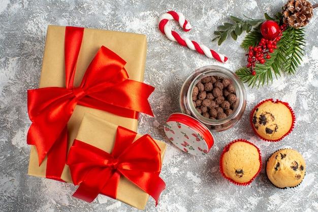 Sopra la vista di deliziosi piccoli cupcakes e cioccolato in un vaso di vetro e rami di abete accanto al regalo con nastro rosso sulla superficie del ghiaccio ice