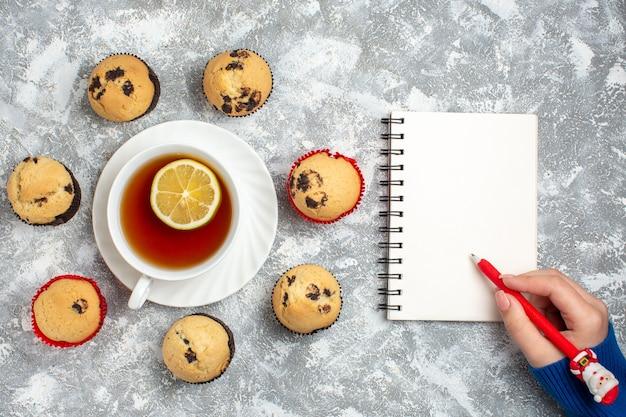 Sopra la vista di deliziosi piccoli cupcakes con cioccolato intorno a una tazza di tè nero e scrittura a mano su un taccuino sulla superficie del ghiaccio