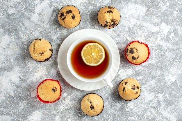 Sopra la vista di deliziosi piccoli cupcakes con cioccolato intorno a una tazza di tè nero sulla superficie del ghiaccio