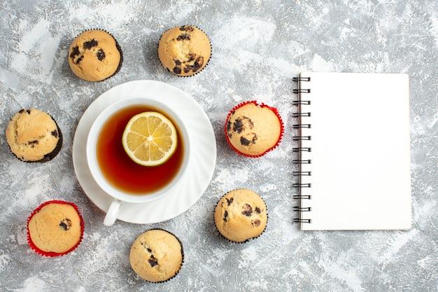 Sopra la vista di deliziosi piccoli cupcakes con cioccolato intorno a una tazza di tè nero accanto al taccuino sulla superficie del ghiaccio