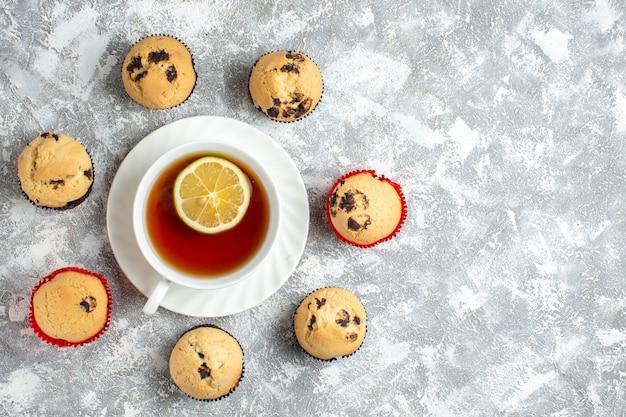 Sopra la vista di deliziosi piccoli cupcakes con cioccolato intorno a una tazza di tè nero sul lato destro sulla superficie del ghiaccio