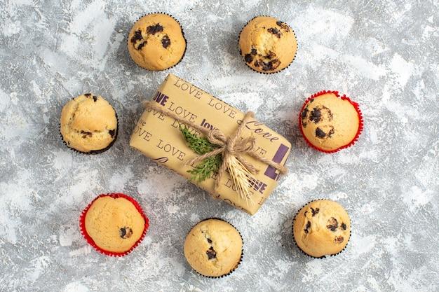 Sopra la vista di deliziosi piccoli cupcakes con cioccolato intorno al regalo con iscrizione d'amore sulla superficie del ghiaccio ice