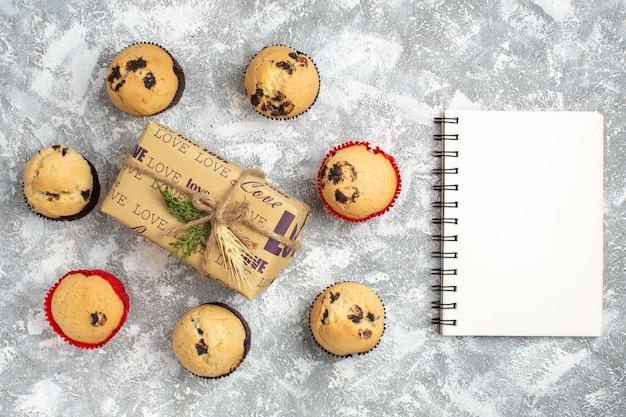 Sopra la vista di deliziosi piccoli cupcakes con cioccolato intorno a un regalo con iscrizione d'amore e taccuino sulla superficie del ghiaccio