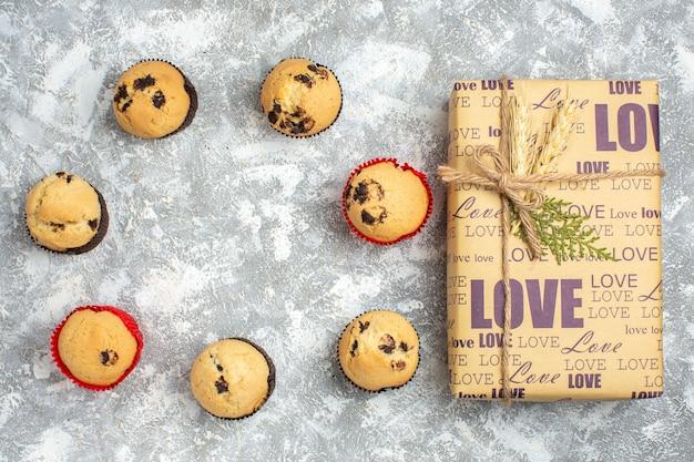 Sopra la vista di deliziosi piccoli cupcakes con cioccolato e regalo con iscrizione d'amore sulla superficie del ghiaccio