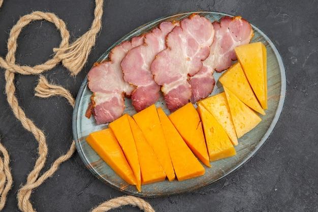 Vista dall'alto di deliziosi snack su un piatto blu e corda su un piatto nero