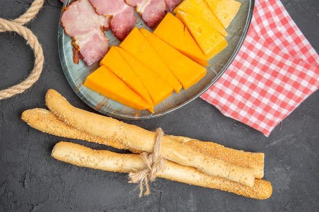 Vista dall'alto di deliziosi snack su un piatto blu e corda sul lato sinistro su un piatto nero