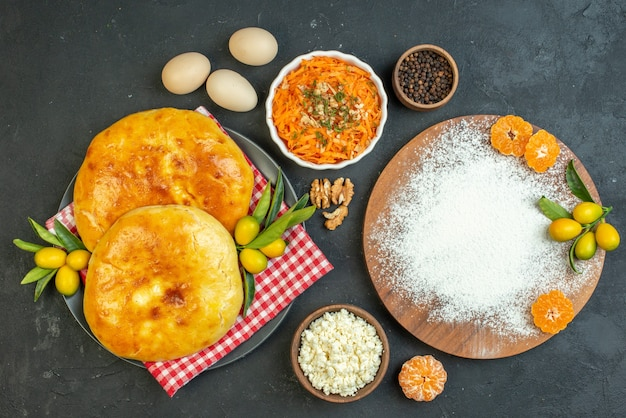 Above view of delicous fresh baked pastries and cheese peppers eggs flour tangerines on the wooden cutting board salad on dark blackground