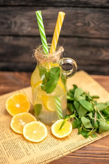 Above view of detox water made of lemon and mint on an old newspaper on brown wooden background