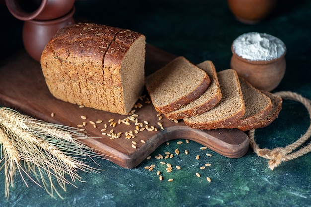 Above view of dietary black bread spikes wheats on wooden cutting board bowls flower pot on blue background