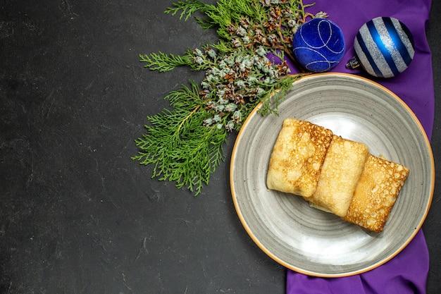 Sopra la vista dello sfondo della cena con deliziose frittelle e accessori decorativi su sfondo nero