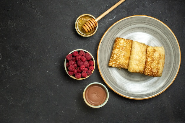 Above view of dinner background with delicious pancakes honey and chocolate raspberry on black background