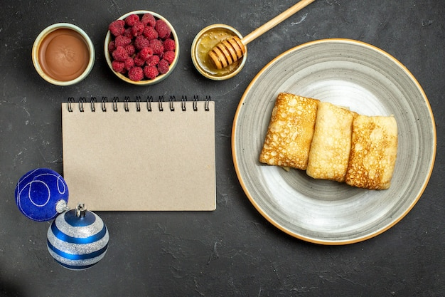 Above view of dinner background with delicious pancakes honey and chocolate raspberry next to notebook decoration accessories on black background