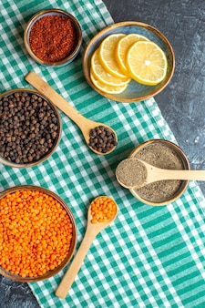 Above view of dinner background with different spices yellow pea on green stripped towel on dark table
