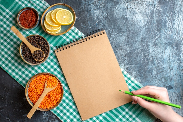Above view of dinner background with different spices yellow pea and hand holding a pen on spiral notebook on dark table