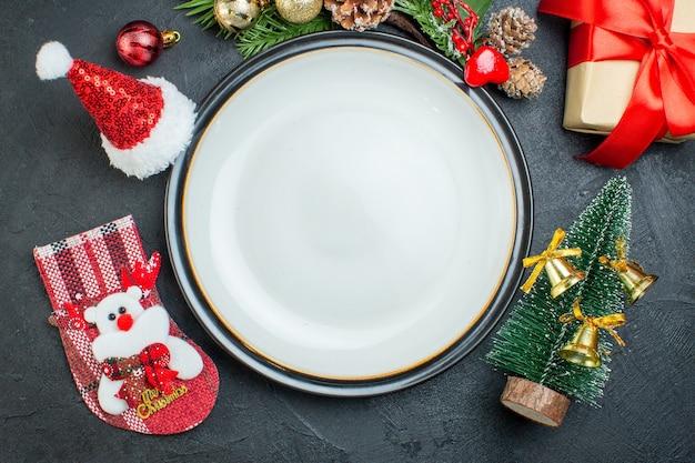 Sopra la vista del piatto di cena albero di natale rami di abete conifera cono confezione regalo cappello di babbo natale calzino di natale su sfondo nero