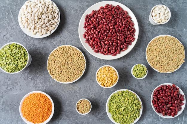 灰色の背景上のエンドウ豆、レンズ豆、豆、豆類の品揃えの真上を表示します。
