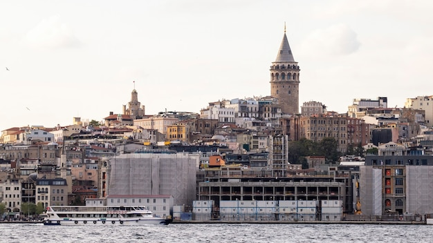 View of a district with residential buildings and galata tower in istanbul, bosphorus strait with moving boat on the foreground, turkey