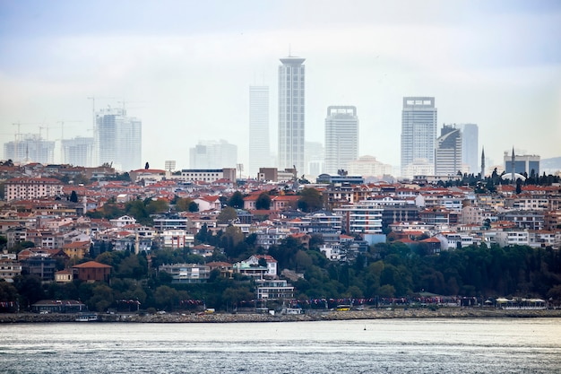 View of a district with residential and high modern buildings in istanbul, bosphorus strait on the foreground, turkey