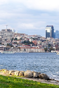 View of a district with residential and high modern buildings in istanbul, bosphorus strait with boats, people resting on the shore, turkey