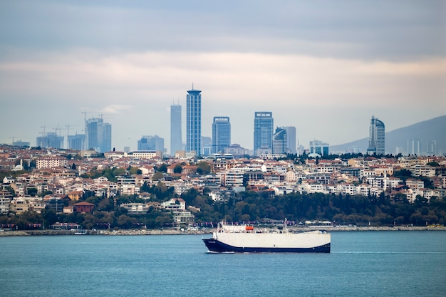 View of a district with residential and high modern buildings in istanbul, bosphorus strait with moving ship on the foreground, turkey